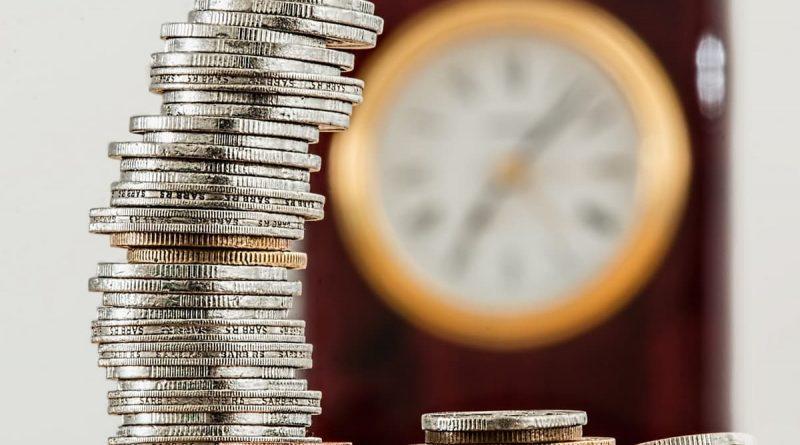 kopa mincí a v pozadí hodiny